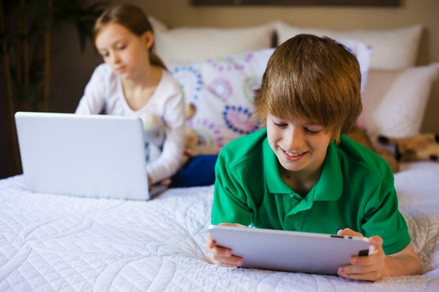 Brother (10-12) and sister (7-9) lying on bed using laptop and tablet --- Image by © Jim Craigmyle/Corbis